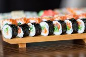 stock photo of soy sauce  - Sushi rolls served on a wooden plate in a restaurant - JPG