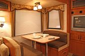 foto of motor coach  - interior of a motor home showing dining table with dishes - JPG