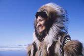 stock photo of eskimos  - Smiling Eskimo woman wearing traditional clothing in wind against clear blue sky - JPG