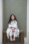 Full length portrait of a young girl in bathrobe sitting on bench by bathtub