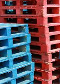 stock photo of wooden pallet  - Closeup of red and blue wooden pallets - JPG