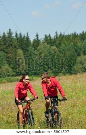 Sportive paar Riding-Mountain-Bike in Wiese