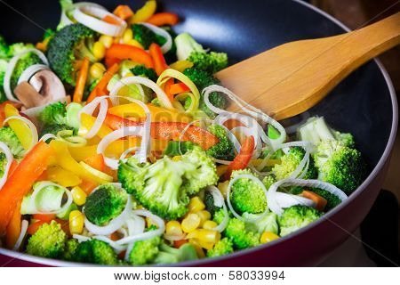 frying vegetables in pan with spatula
