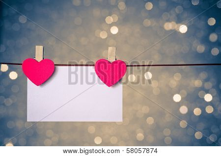 Two Decorative Red Hearts With Greeting Card Hanging On Blue And Golden Light Bokeh Background, Conc