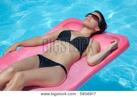 Woman In Black Bikini Floating On Back