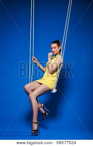 Image of flirtatious disco girl posing on swing
