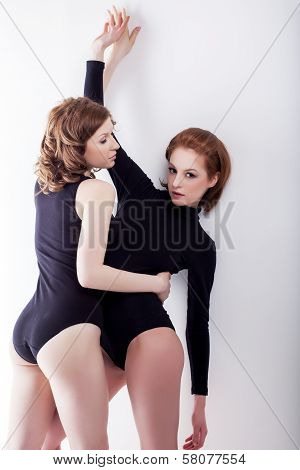 Attractive bisexual girlfriends hugging in studio