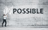 "pic of impossible  - Man turning the word ""Impossible"" into ""Possible""