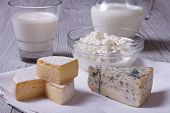 stock photo of brie cheese  - set of products brie blue cheese cottage cheese and milk on the table closeup - JPG