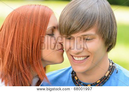Loving young woman kissing boyfriend's cheek sunny day close-up