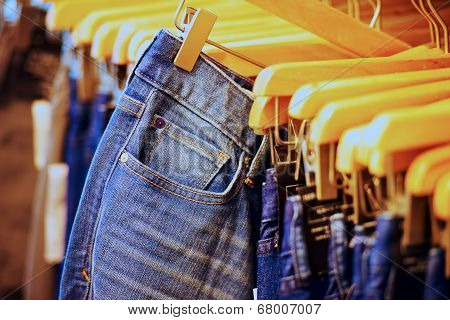 Row of hanged blue jeans in a shop