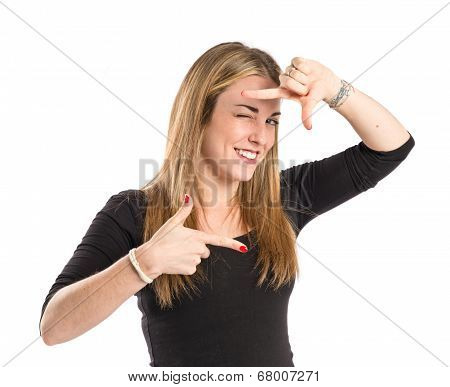 Blonde Girl Focusing With Her Fingers On A White Background