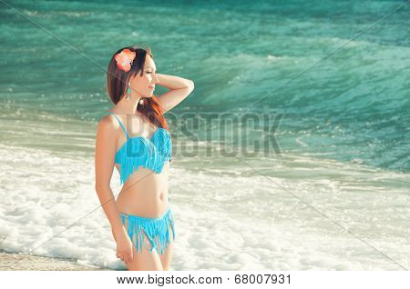 Slim beautiful woman on the sea coast looking into distance
