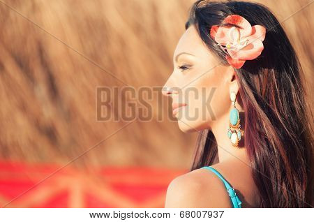 Face close-up of beautiful girl with orchid in her hair
