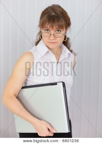 Serious Girl Holds Closed Laptop In Hand