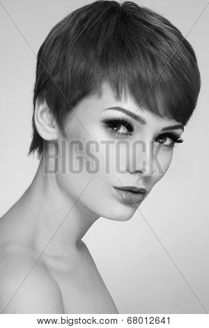 Black and white portrait of young beautiful woman with stylish short haircut and extended lashes