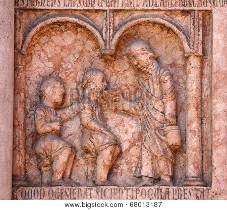 PARMA,ITALY-MAY 01,2014:Christ Performing Works of Mercy relief at the  baptistery from Benedetto Antelami.Baptistery in Parma is considered to be among the most important Medieval monuments in Europe