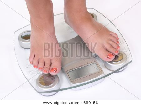 A Pair Of Female Feet Standing On Scale