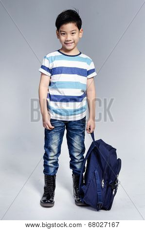 Little Asian Child Standing With A Kit Bag Slung