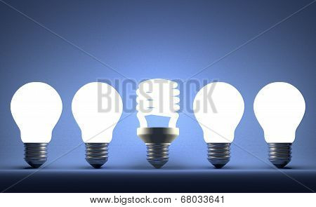 Glowing Spiral Light Bulb In Row Of Tungsten Ones On Blue