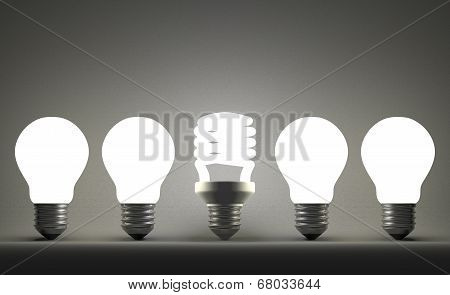 Glowing Spiral Light Bulb In Row Of Tungsten Ones On Gray
