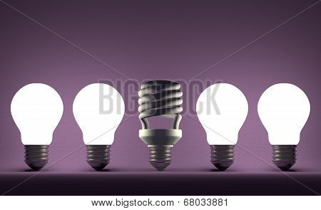Dead Spiral Light Bulb In Row Of Glowing Tungsten Ones On Violet
