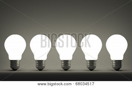 Row Of Glowing Tungsten Light Bulbs On Gray