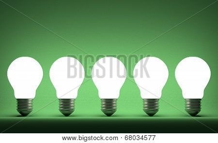 Row Of Glowing Tungsten Light Bulbs On Green