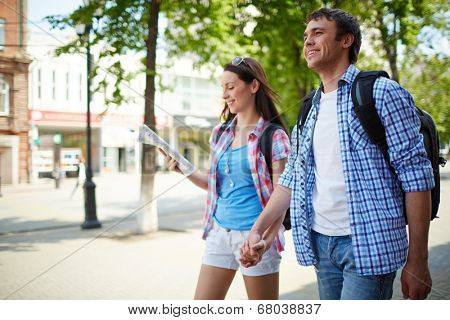 Couple of young travelers taking walk during journey