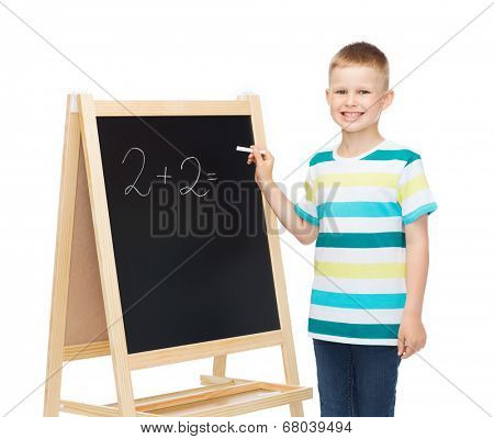 people, childhood, mathematics and education concept - happy little boy with blackboard and chalk writing math exercise