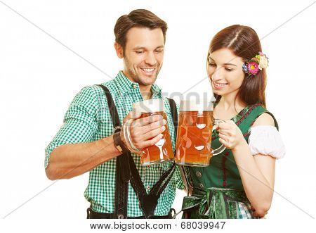 Happy couple in traditional outfit drinking beer in Bavaria at Oktoberfest