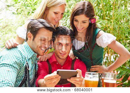 Happy friends taking selfie in bavarian beer garden in summer