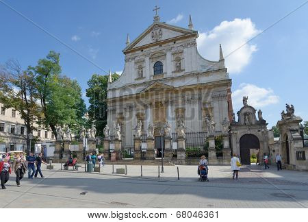 KRAKOW, POLAND - SEPTEMBER 15, 2013: People under the Church of Saints Apostles Peter and Paul known best for the statues of the 12 disciples lining the fence. It's the first baroque church in Krakow