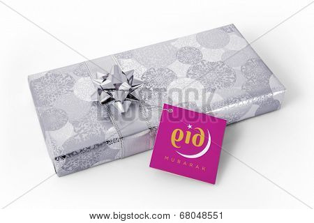 A pink tag attached to a silver gift box with message 'Eid Mubarak'