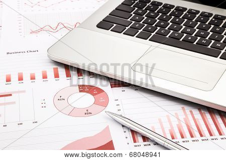 Laptop And Pen With Red Business Charts, Graphs, Infomation And Reports