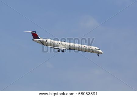Delta Connection Bombardier CRJ-900 in New York sky before landing at JFK Airport