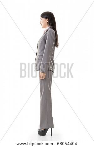 Full length portrait of Asian business woman wear pant suit, side view isolated on white background.