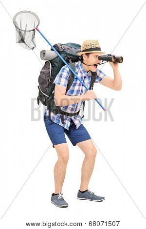 Full length portrait of a guy with butterfly net looking through binoculars isolated on white background