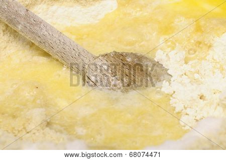 Wooden spoon mixing flour egg