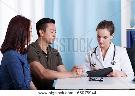 Asian Couple During Visit At Doctor's Office