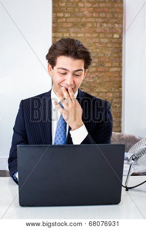 Businessman Snickering At His Laptop