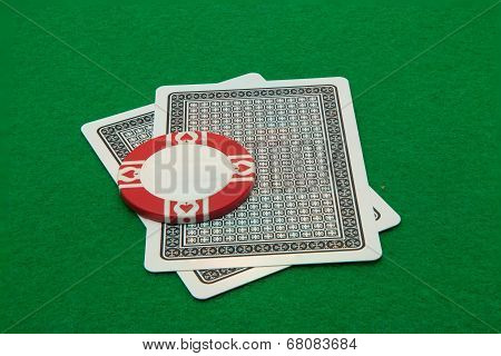 Two cards facing down with casino chip on green background