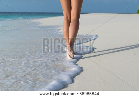 Beach travel - woman walking on sand beach leaving footprints in the sand. Closeup detail of female
