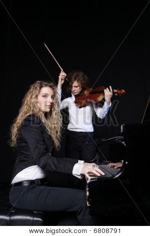 Two Beautiful Young Women Posing With Violin And Piano