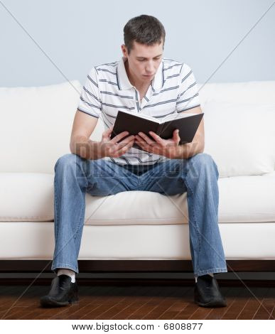 Young Man Sitting On Sofa Reading