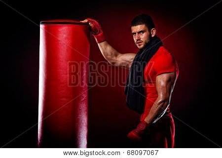 young man standing by bag boxing in studio