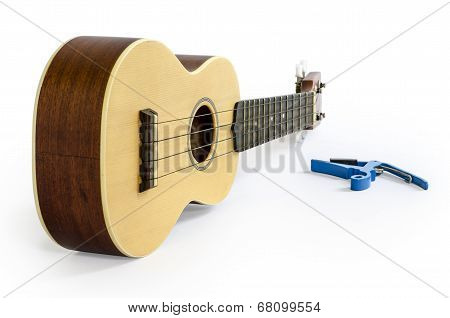 Ukulele and Capo isolated on white Clipping path included : does not include shadow