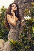 picture of magnolia  - fashion photo of beautiful glamour model with luxurious curly hair in elegant beige dress posing beside a magnolia tree at summer garden - JPG