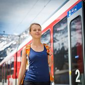 Young woman traveling by train, happy to have reached her destination poster