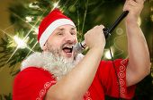 pic of christmas song  - Bearded mature man in Santa Claus costume belting Christmas songs with microphone - JPG